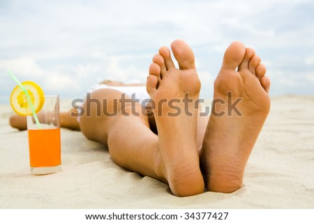 Close-up of two human feet on sandy beach with cocktail near by