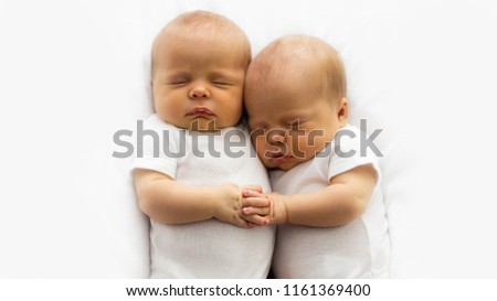 Close-up of two identical twin one month old infant babies cuddling together holding hands with fingers intertwined. Room for text on sides.