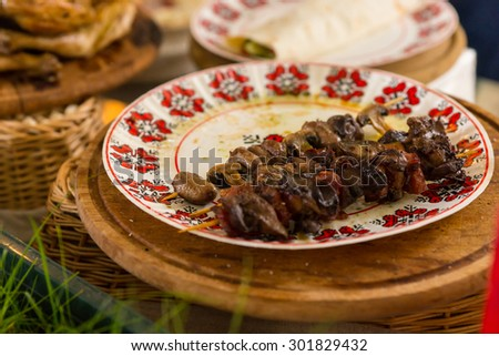 Close Up of Two Left Over Grilled Kebab Skewers on Floral Print Plate on Table Amongst Other Dishes