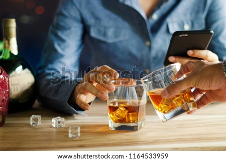 Close-up of two men clink glasses of whiskey drink alcoholic beverage together while at bar counter in the pub #1164533959