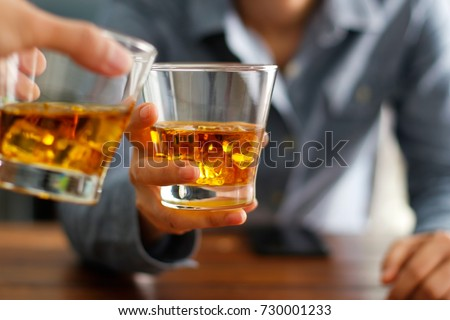 Close-up of two men clink glasses of whiskey drink alcoholic beverage together while at bar counter in the pub #730001233
