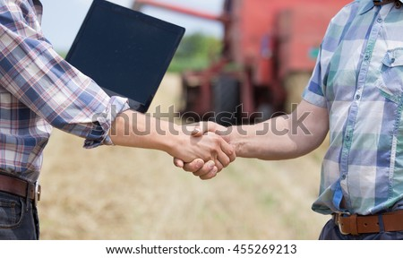 Close up of two men in plaid shirts shaking hands on the farmland. Combine harvester working in background
