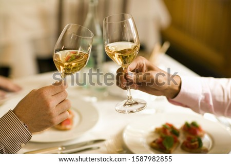 Close up of two men toasting with wine at restaurant