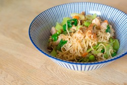 Close-up of two-minute noodle dish heaped with chicken pieces and fresh asian vegetables including bok choy, edamame beans and carrots, with rich satay sauce
