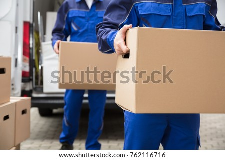 Close-up Of Two Mover's Hand In Uniform Carrying Cardboard Box #762116716