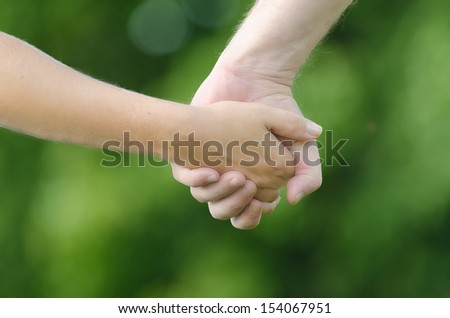 Close-up of two people (man and woman) holding hands on green background. A symbol of love, connection, closeness, relationship and friendship. Natural lightning of summer time.