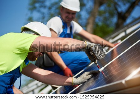 Close-up of two professional technicians connecting solar photo voltaic panel to metal platform on blue sky background. Stand-alone solar system installation, efficiency and professionalism concept.