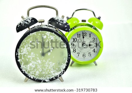 close up of   two retro alarm clocks, black and green, showing winter time and summer time, 2 am, 3 am, horizontal / Clock Change Winter Time