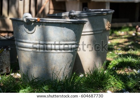 Close up of two rusty iron buckets in grass in the garden. Dirty gray metallic bucket with garbage on barnyard at sunny day. Gardening background. Containers for storing feed, trash, water, paint