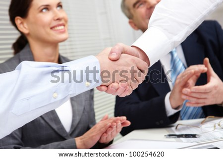 Close-up of two shaking hands against business team