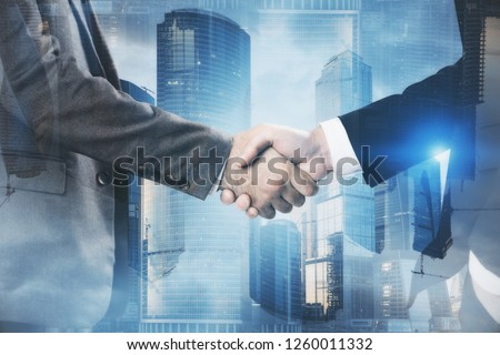 Close up of two unrecognizable businessmen shaking hands over blue Moscow city panorama. Concept of partnership. Toned image double exposure
