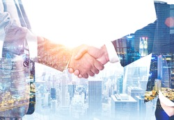 Close up of two unrecognizable businessmen shaking hands over modern cityscape background. Concept of partnership. Toned image double exposure