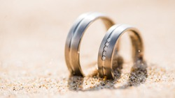 Close up of two wedding rings in the sand