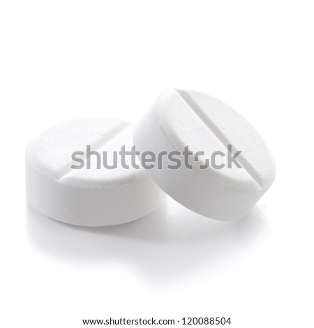 Close-up of two white pills on white background