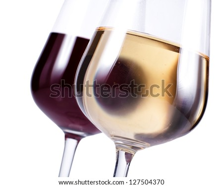 close up of two wine glasses with red and white wine isolated over white