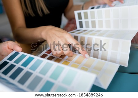 Close-up of two women choosing samples of wall paint. Interior designer consulting a client looking at a color swatch. House renovation concept Foto stock ©