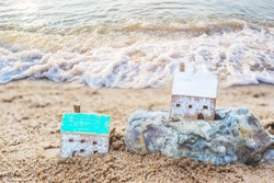 Close up of Two Wooden houses model on the rock and sand with soft wave from seascape background, Christian concept wise man build house on the rock but foolish man built house on the sand