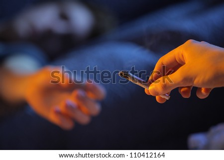 Close up of two young adults smoking a joint