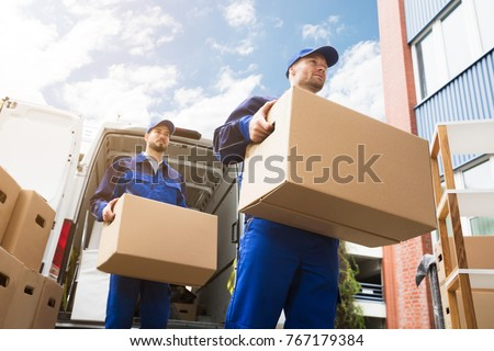 Close-up Of Two Young Delivery Men Carrying Cardboard Box In Front Of Truck