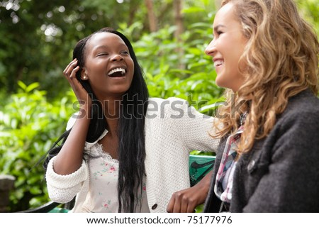 Close-up of two young female friends gossiping in park