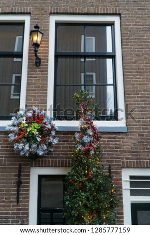 Close up of typical dutch building front, with its bricks, white windows & street lantern, during Christmas with decorated crown & lighted fir tree with tinsel & fairy lights, Netherlands, Holland. #1285777159