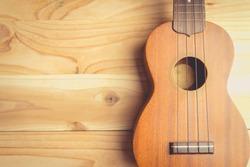 Close up of ukulele on old wooden background , vintage tone