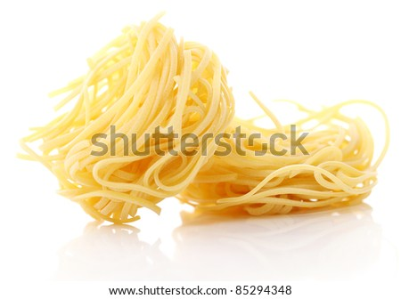 Close up of uncooked nest pasta against white background