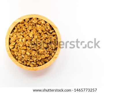 Close up of uncooked rolled oats (oat flakes) in wooden bowl isolated on white background. Concept : Healthy food ,Vegan food ,Raw food.
