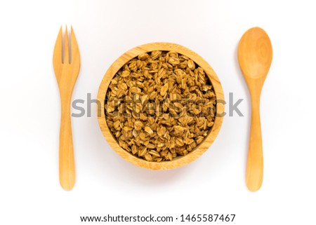 Close up of uncooked rolled oats (oat flakes) in wooden bowl with wooden spoon and fork isolated on white background. Concept : Healthy food ,Vegan food ,Raw food.