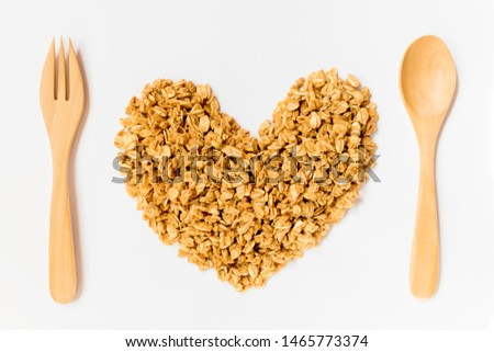 Close up of uncooked rolled oats (oat flakes) shape form heart with wooden spoon and fork isolated on white background. Concept :Love healthy food ,Vegan food ,Raw food ,Valentine 's day.