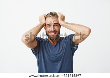 Close up of unhappy handsome guy with beard holding hair with hands, being super disappointed about broken new smartphone. #721915897