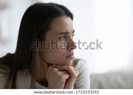Close up of unhappy millennial girl look in window distance thinking or pondering, upset thoughtful young woman lost in thoughts, feel lonely melancholic, yearn after marriage dissolution or breakup