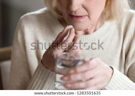 Close up of unhealthy middle aged woman suffers from pain, holding pill and glass of still water feels ill taking medicine, cropped image. Disease prevention and treatment of old mature people concept