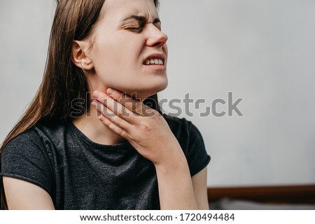 Close up of unhealthy young woman touch neck hard to swallow having discomfort or painful feeling sitting on bed at home, unwell sad girl suffering from angina, sore throat, experience loss of voice Stock photo ©