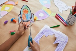 Close up of unrecognizable African-American boy cutting picture of space rocket while enjoying art and craft class in school or children development center, copy space