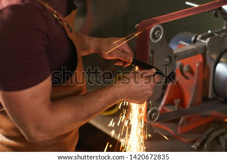 Close-up of unrecognizable artisan in apron using knife grinding jig to sharpen knife blade in smithy