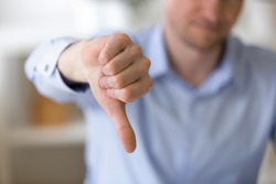 Close up of unrecognizable businessman with dissatisfied face showing negative sign, dislike with thumbs down, rejection concept at workplace, sign no, not approved, unhappy customer