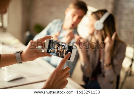 Close-up of unrecognizable woman taking a photo with smart phone of playful coworkers in the office.