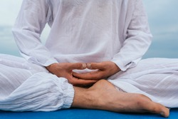Close up of unrecognized man sitting in yoga mat in the beach meditating..