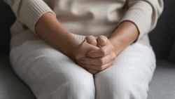 Close up of upset mature woman sit on sofa hold hands joined clenched on laps feel worried at home alone, pensive elderly female anxious about decision, thinking or pondering, elderly solitude concept