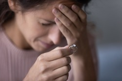 Close up of upset young woman hold wedding ring disappointed with marriage dissolution, unhappy sad millennial Caucasian female suffer after cheating or breakup, frustrated with relationships problems