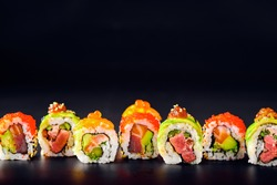 Close-up of uramaki sushi rolls with red caviar, salmon, tuna, cucumber and avocado isolated on black background. Delicious traditional japanese food with sushi rolls.