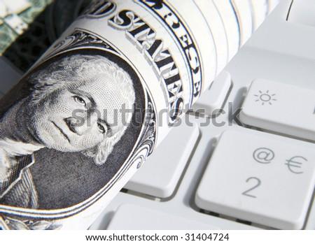 Close-up of US Dollar overlaid over laptop keys