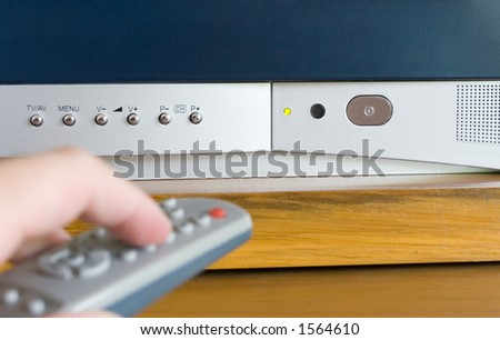Close-up of various buttons/LED light on a TV and with a blurred remote control in the foreground