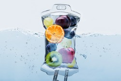Close-up Of Various Fruit Slices In Saline Bag Dip In Water Against White Background