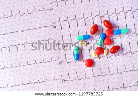 Close up of various types of pills, tablets and drugs on electrocardiogram (EKG or ECG paper) background for health care and medical concept. Top view, copy space, saturated color #1197785725