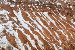 Close up of vertical snow streaks along red rock mountain face in rural New Mexico