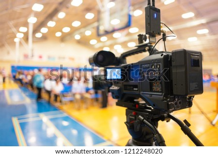close-up of video camera pointed at audience in town hall meeting. #1212248020