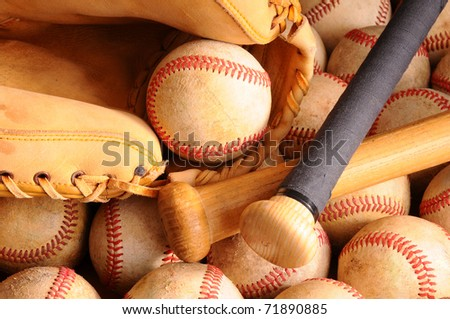 Close up of Vintage Baseball equipment. Horizontal Format with two wooden bats and catchers mitt on top of a pile of old worn baseballs.