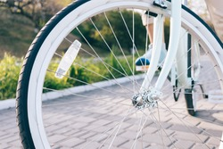 Close-up of vintage Bicycle wheels with white tires and reflector on the chrome spokes